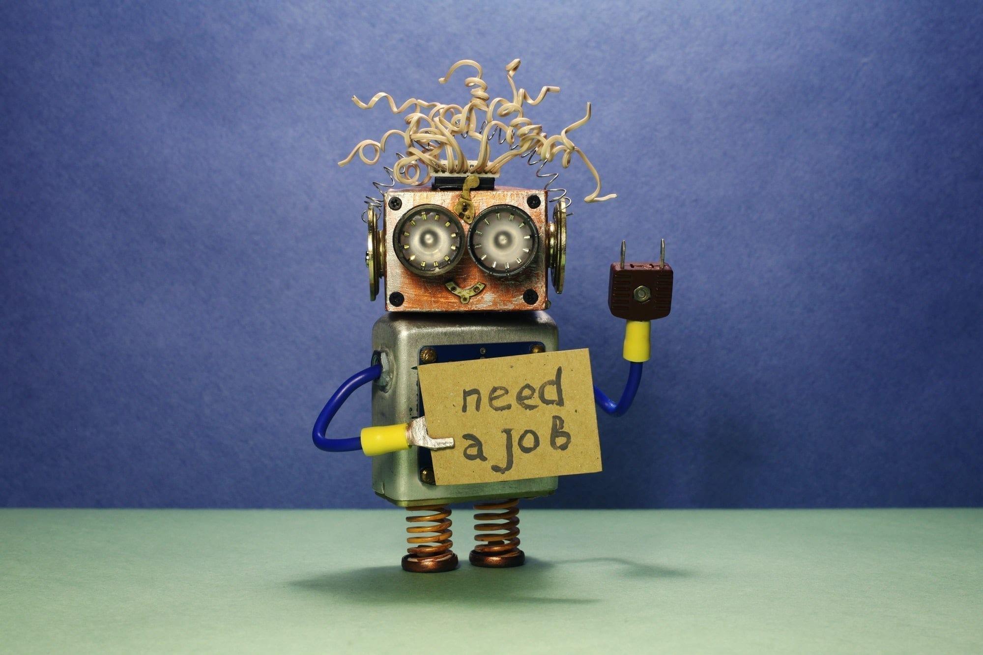 Cartoon robot holding a need a job sign