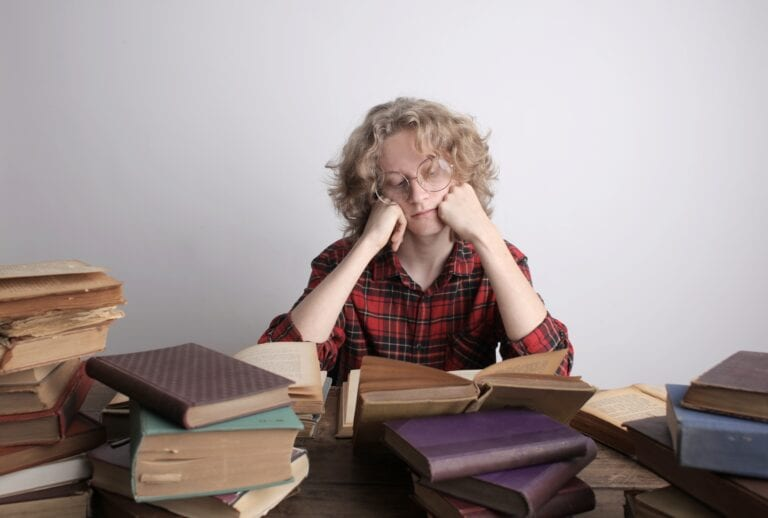 A woman surrounded by piles of books with her head on her hands, looking bored