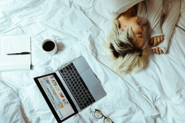 Woman asleep on her bed surrounded by her laptop and coffee