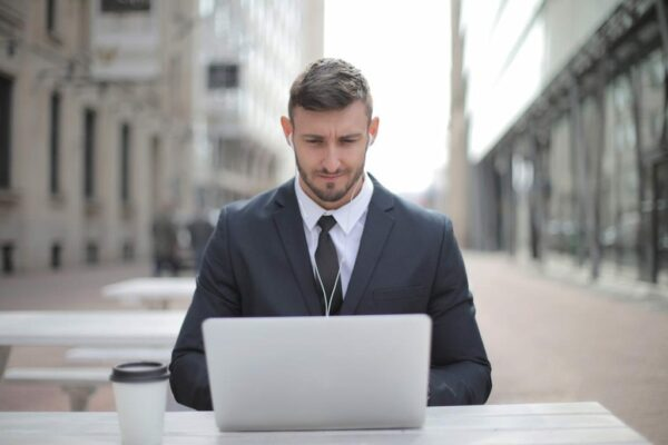 Man at an outside table on his laptop with earphones in