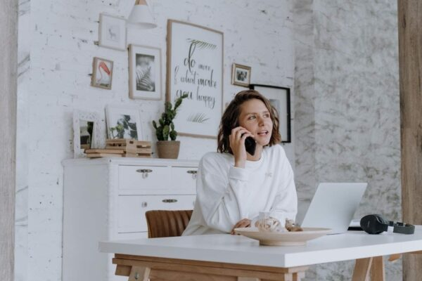 Woman in a white home office on the phone