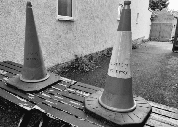 Black and white picture of traffic cones labelled with Covid 19 No Entry