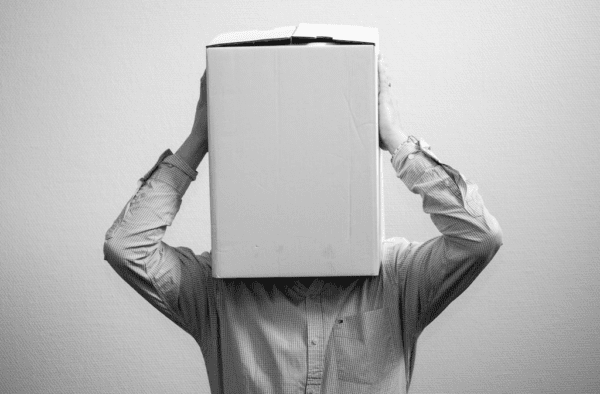 Black and white picture of man with white cardboard box over his head