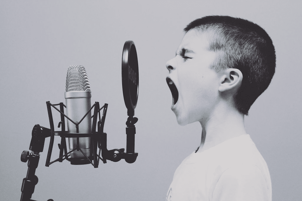 Black and white picture of young boy shouting into recording-style microphone