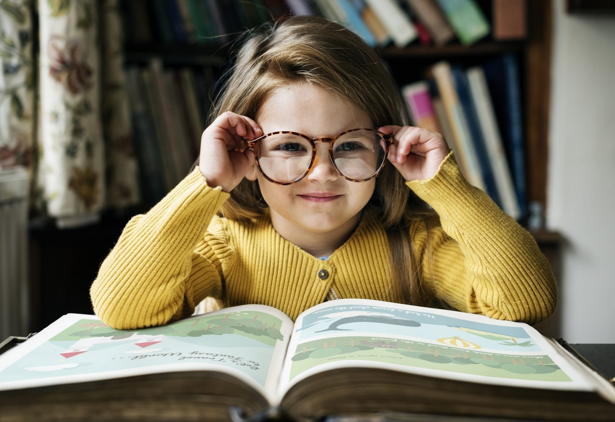 A young girl in glasses smiling with an open book in front of her