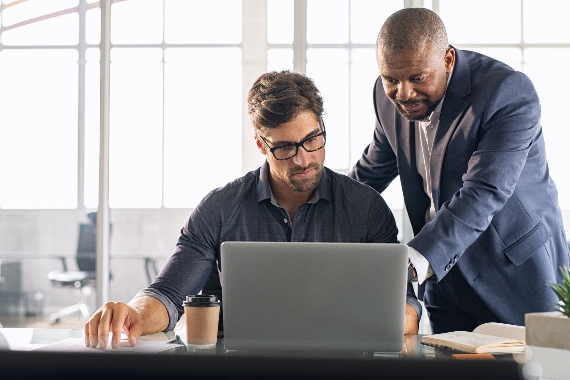 Two men around a laptop, one showing the other what to do