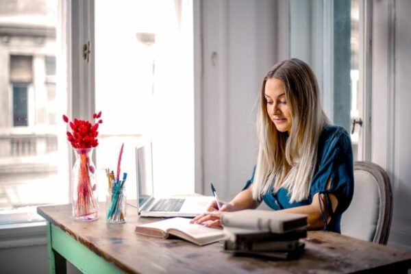 Woman writing in a notepad at her home desk with her laptop open and books on the desk