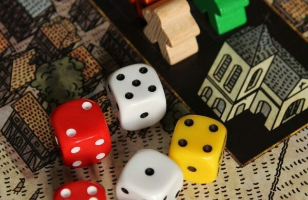 Multi-coloured dice and wooden counter pieces, team building activity