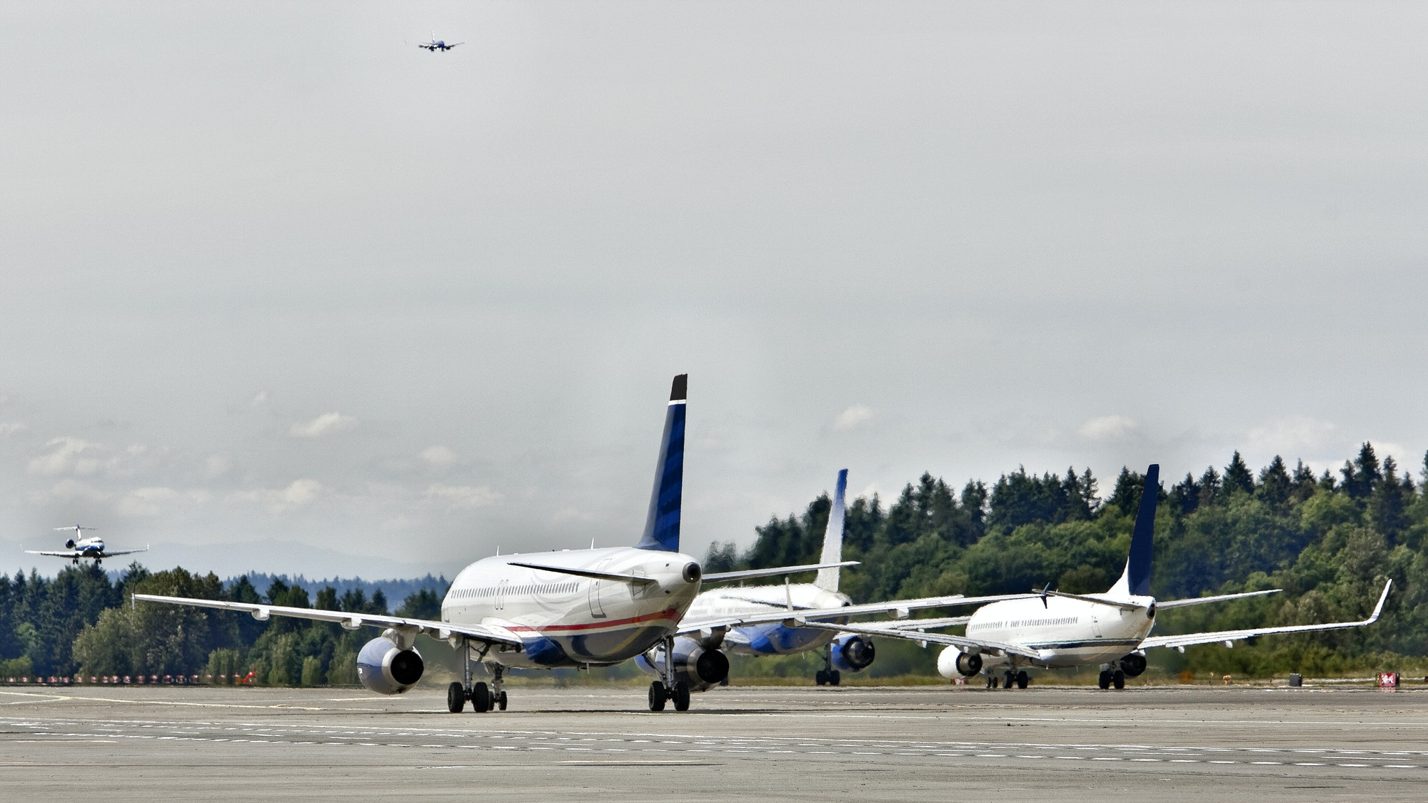 Three airplanes on a runway at an airfield