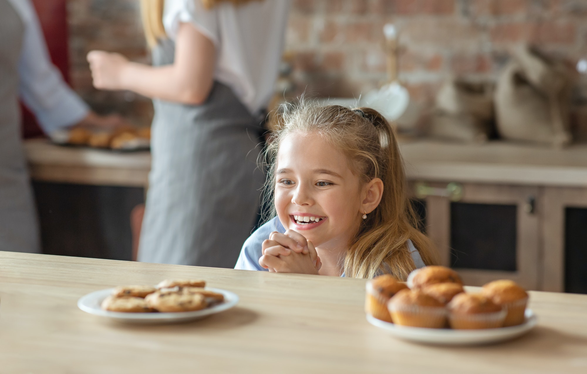Adorable little girl looking with desire at treats on a table