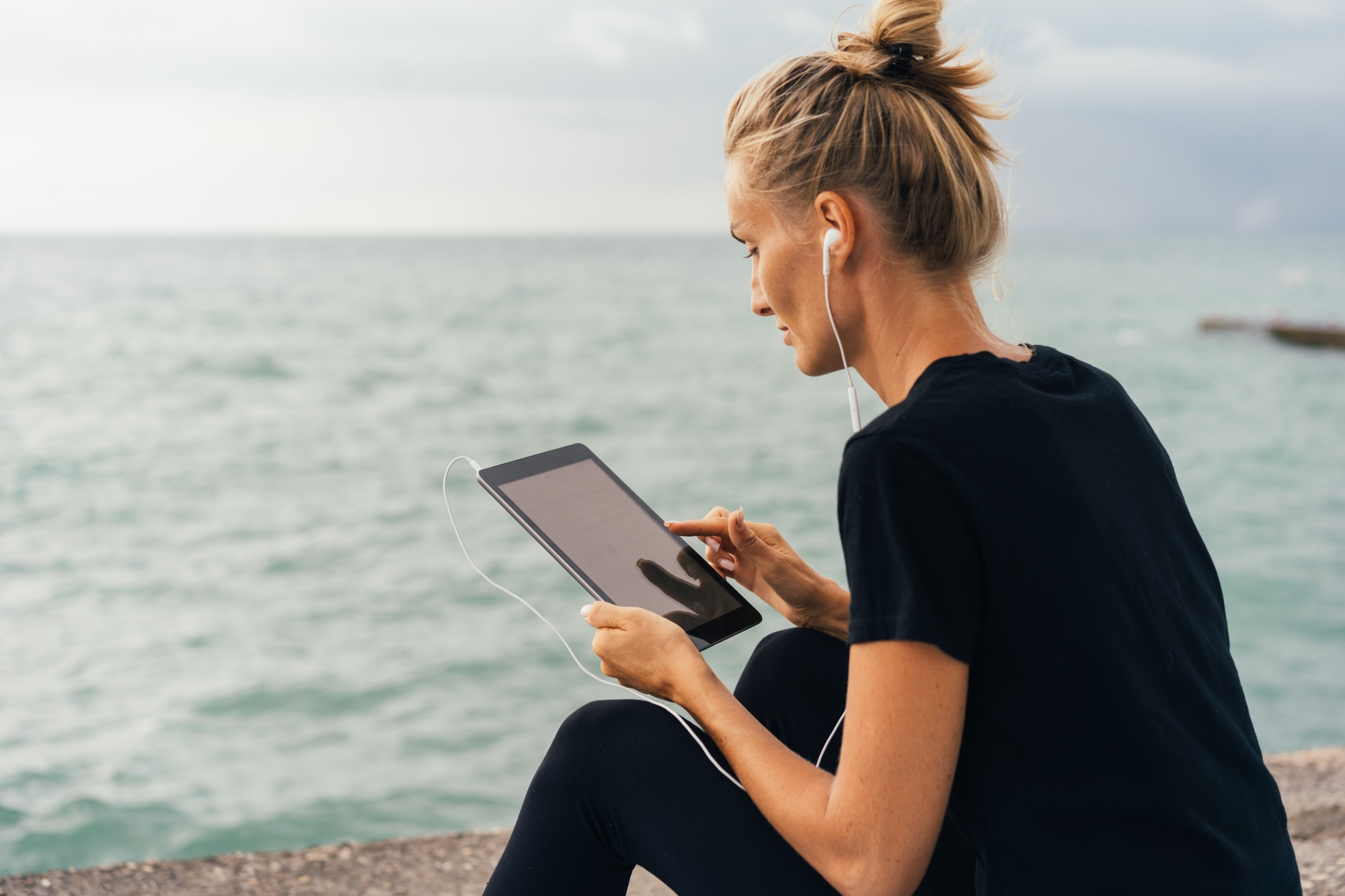 Woman sitting on the beach watching something on her tablet