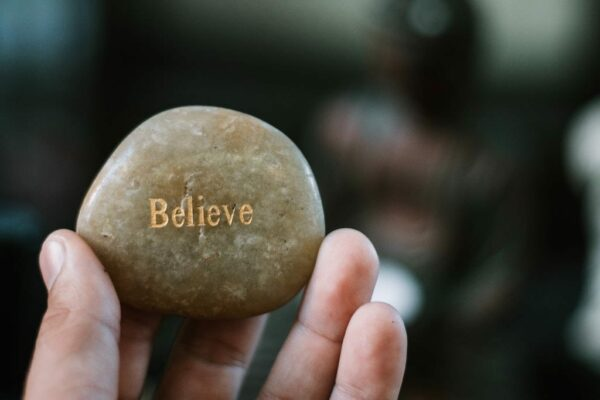 A stone with the word Belief engraved on it