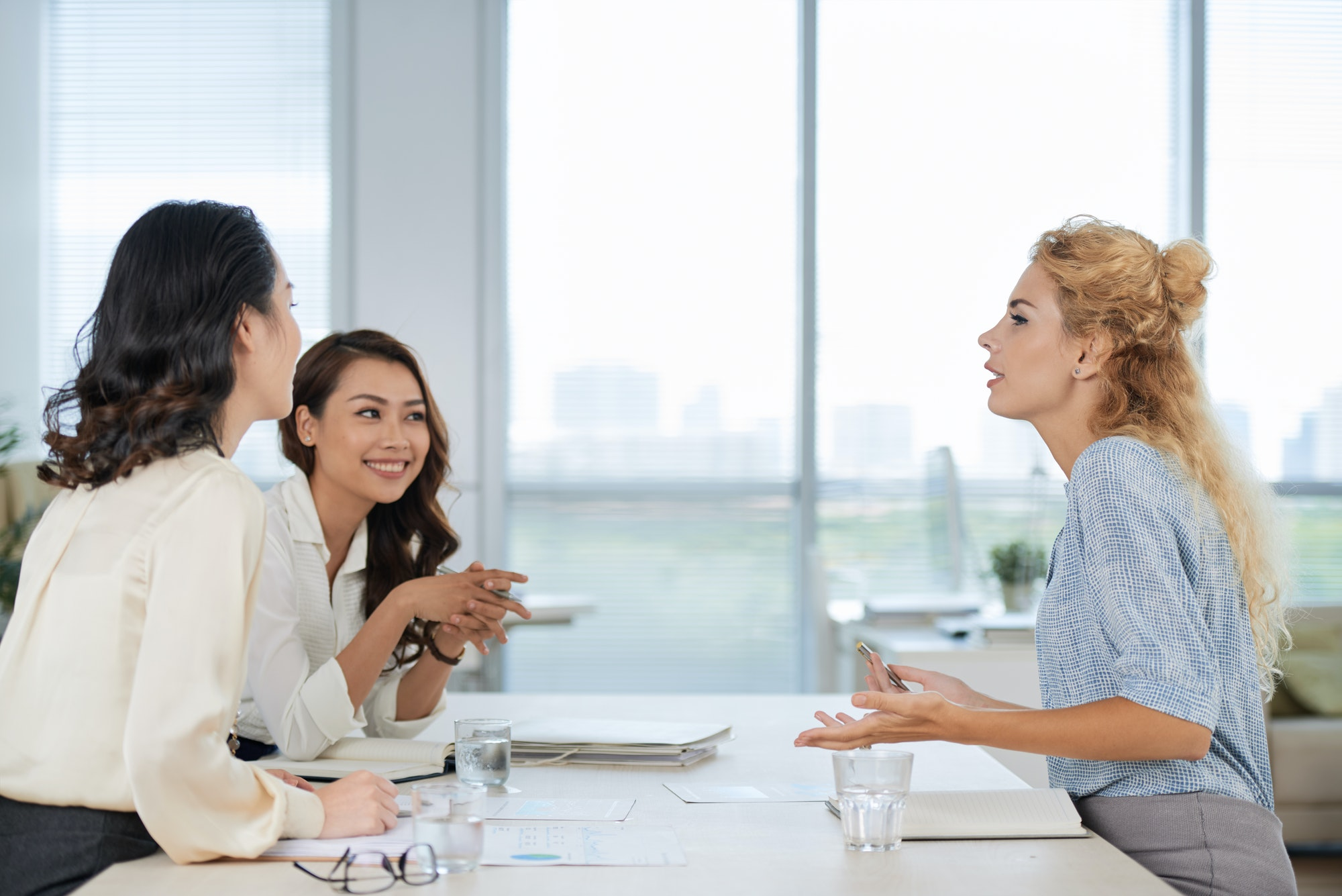 Three female co-workers having a discussion around a table