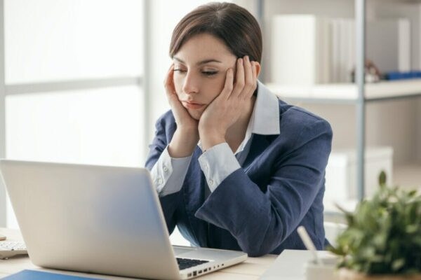 Businesswoman sat at desk looking bored