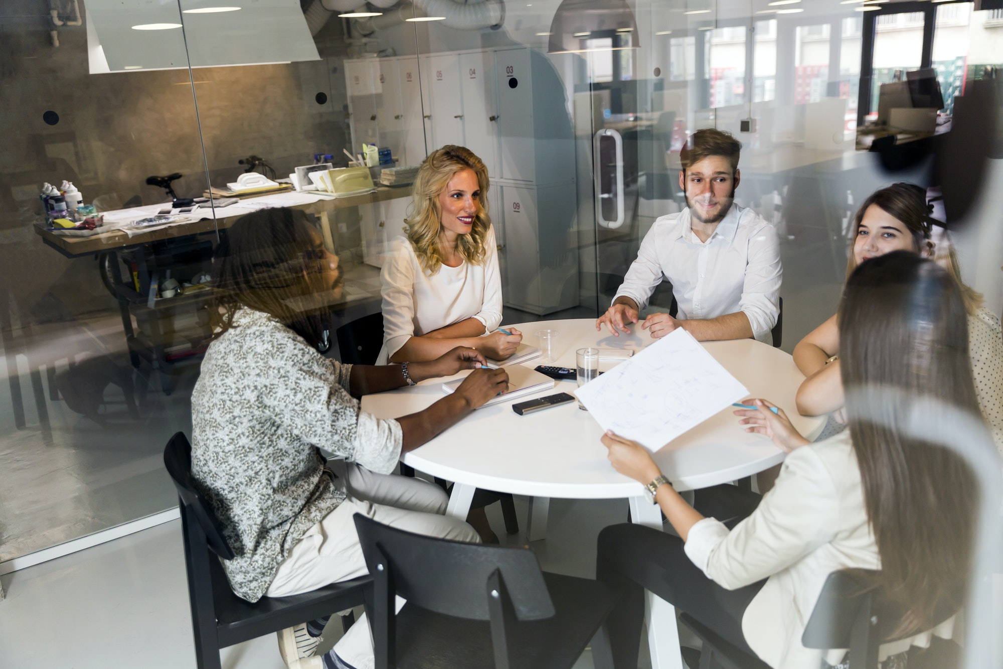 Five co workers around a table having a meeting