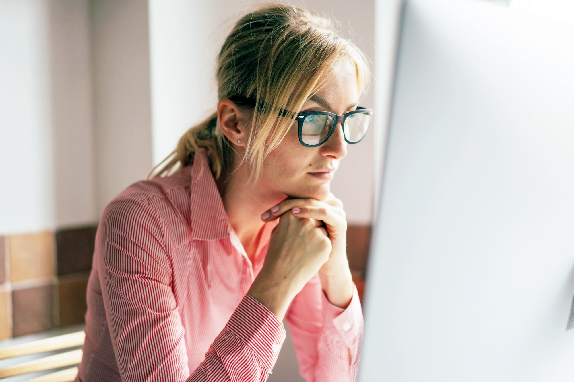 Woman wearing glasses concentrating on her computer screen