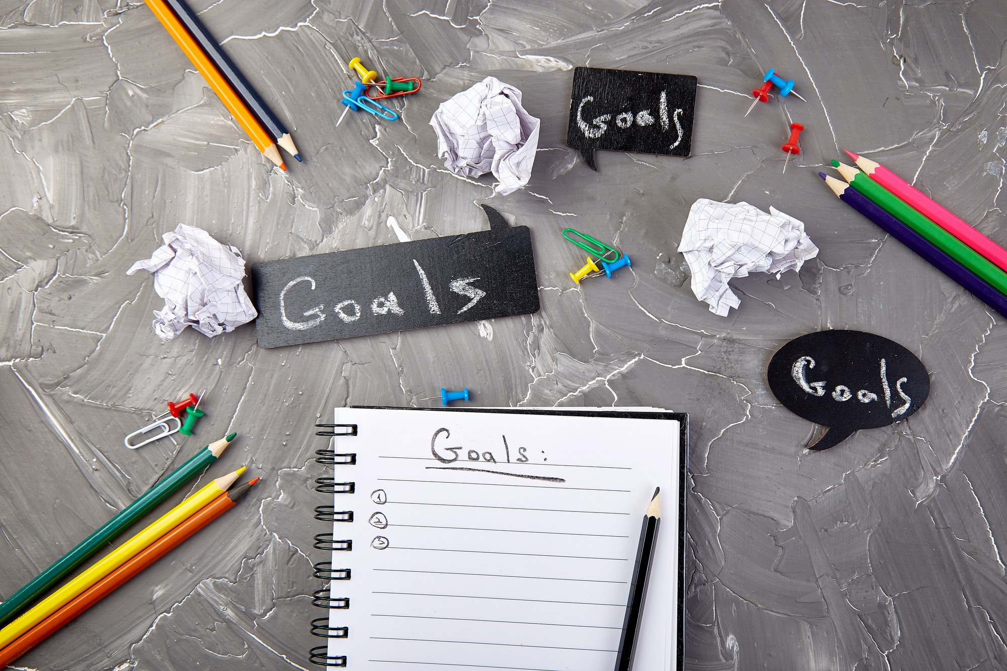 A notepad for writing down goals, with pencils and scrunched up paper around the notepad