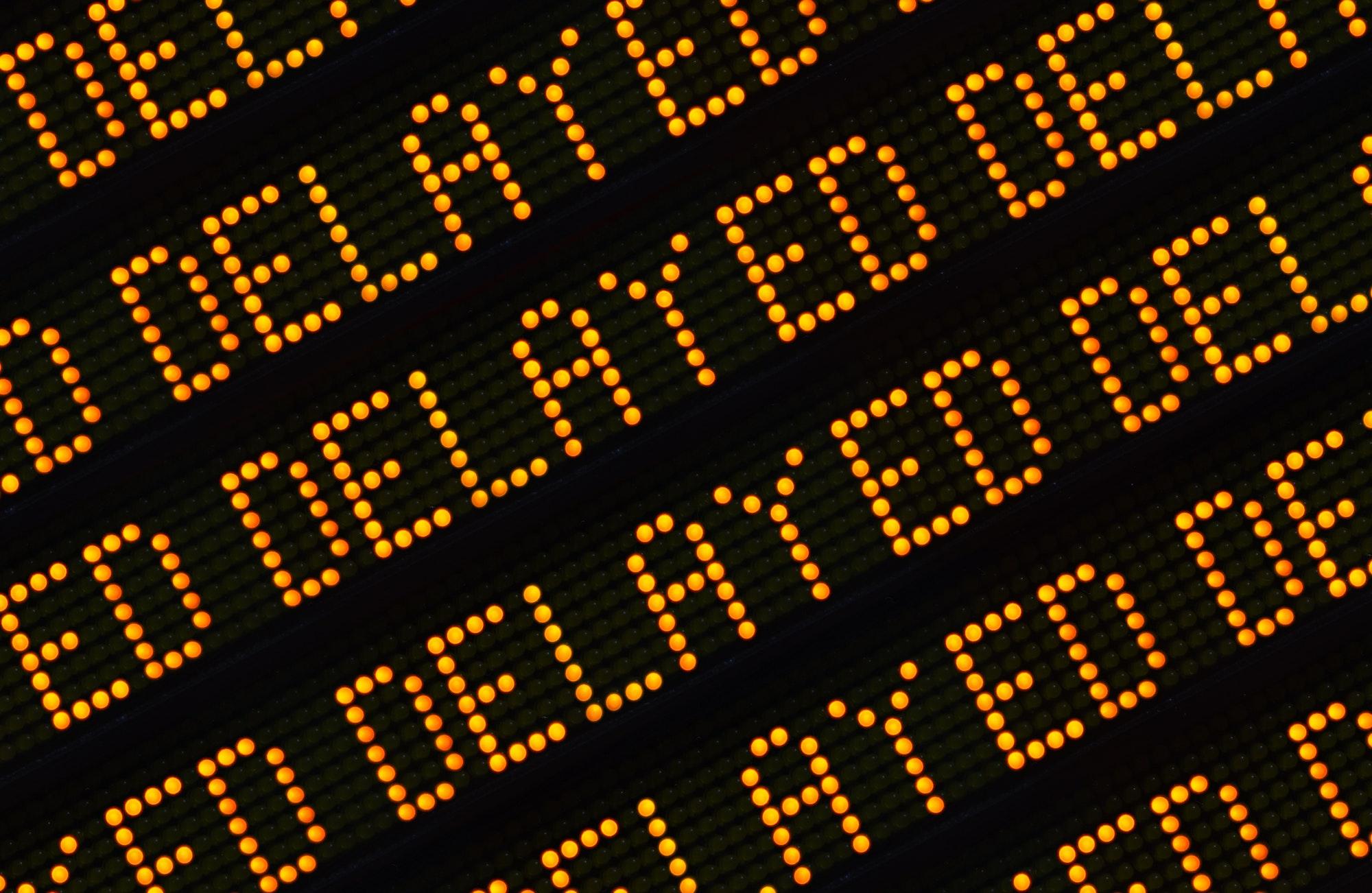 A 'Delayed' sign Closeup, in yellow block capitals, digital form