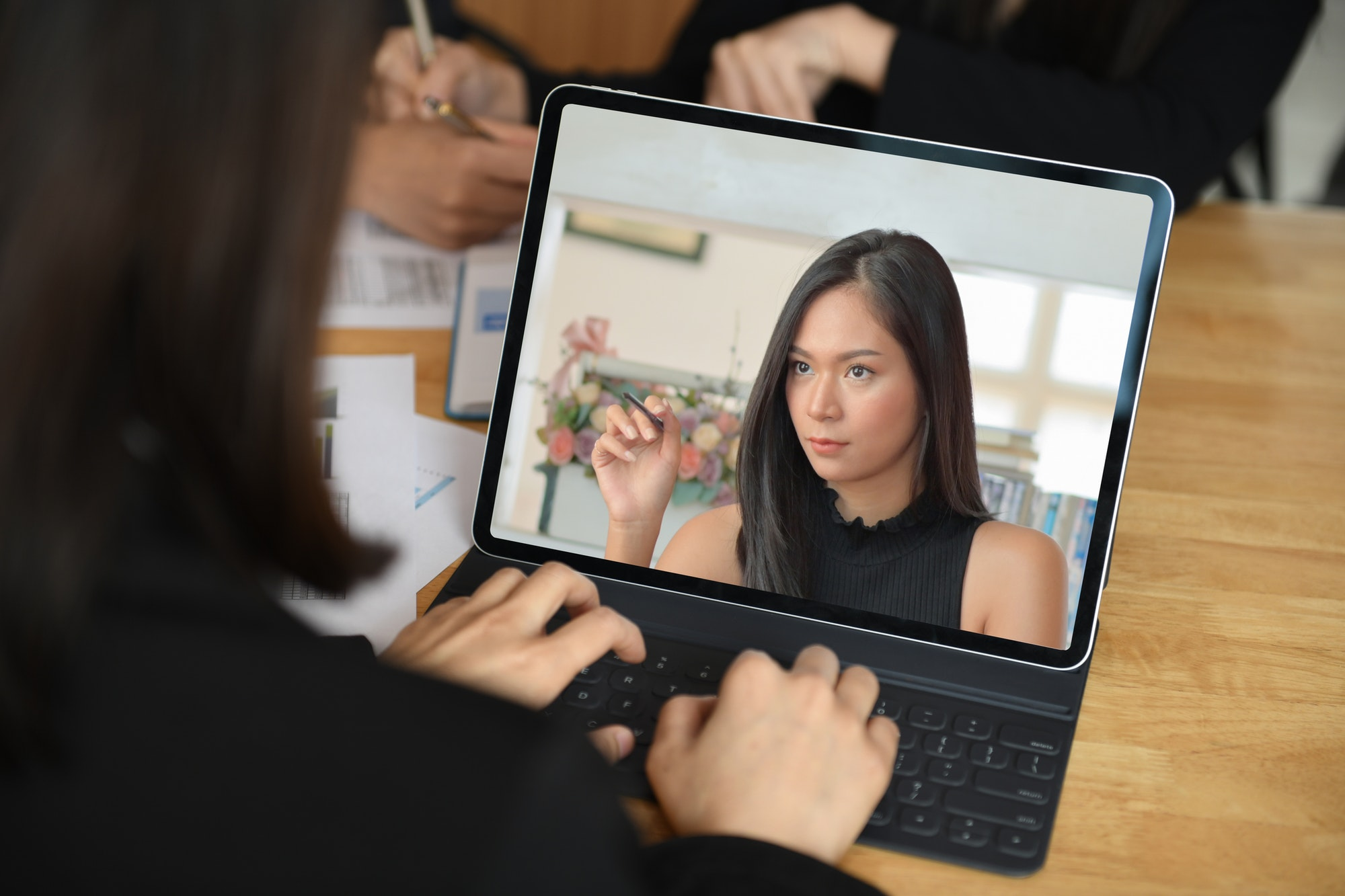 A woman on a laptop, seemingly video calling another (possible fellow employee) who is visually perturbed by something