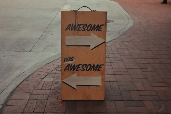 Wooden sign in street with Awesome pointing right and Less Awesome pointing left