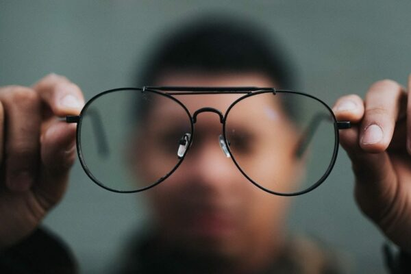 Man holding up glasses with glasses in focus and man is blurry