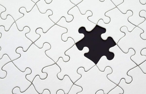 A white jigsaw puzzle with one piece missing