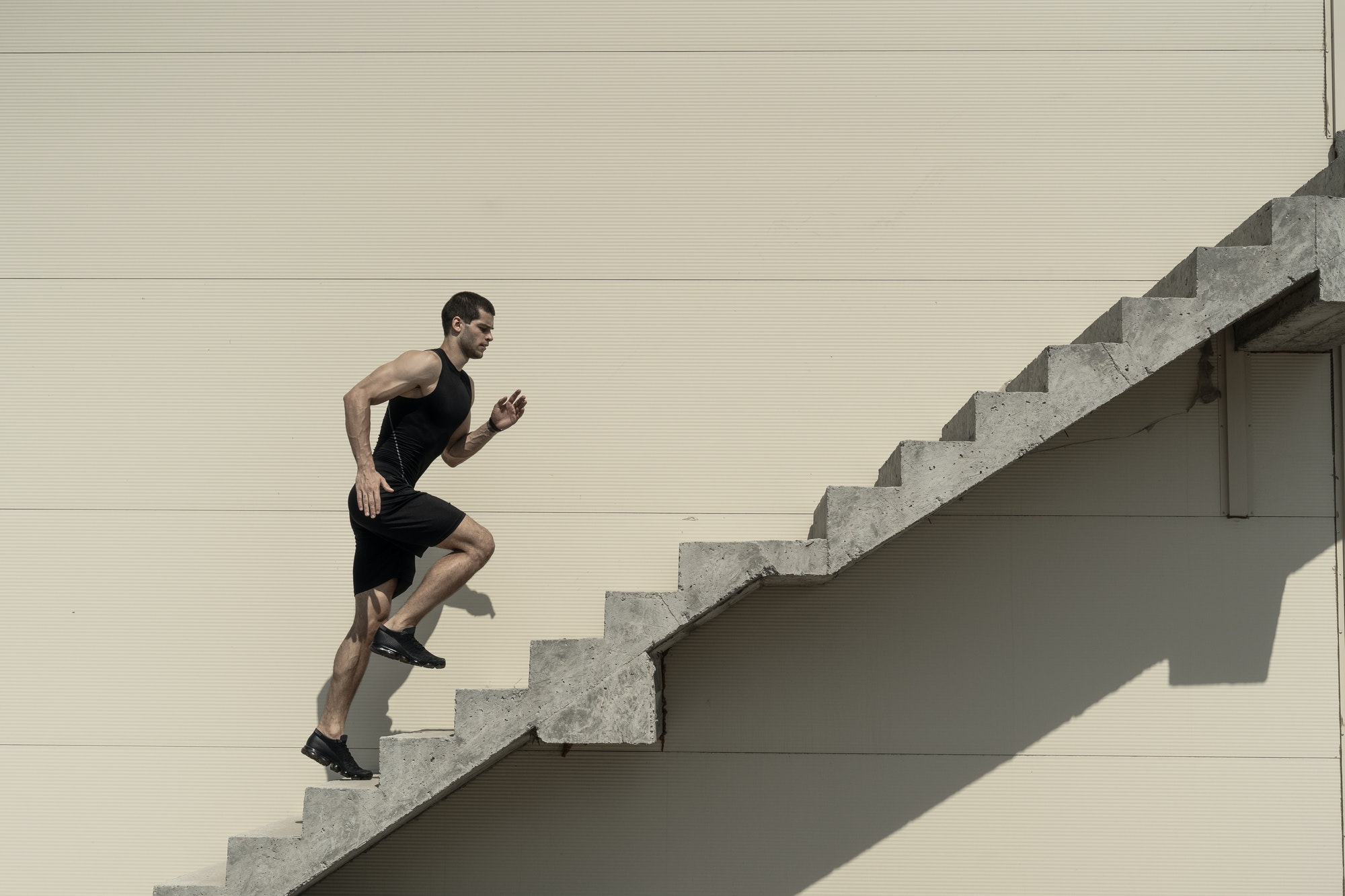 A man in gym wear running up stone stairs, overcoming a challenge