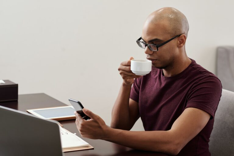 Man checking notifications whilst having a coffee