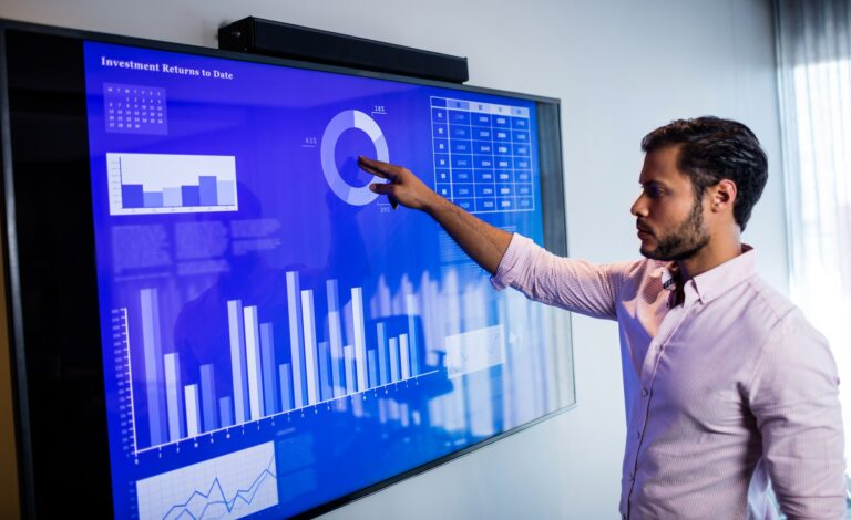 Businessman analysing data on an electronic touch screen