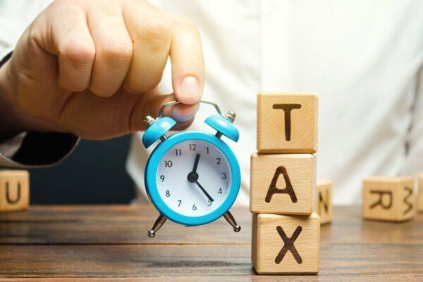 Building blocks spelling tax next to small alarm clock