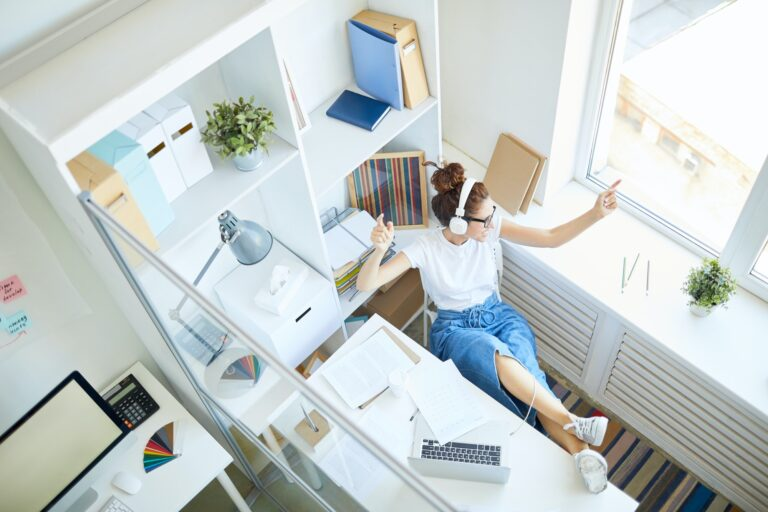 Woman working from home with headphones on, looking out of the window, being distracted