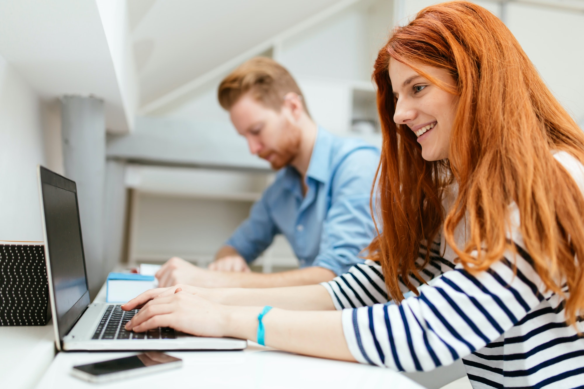 A husband and wife working from home on their laptops