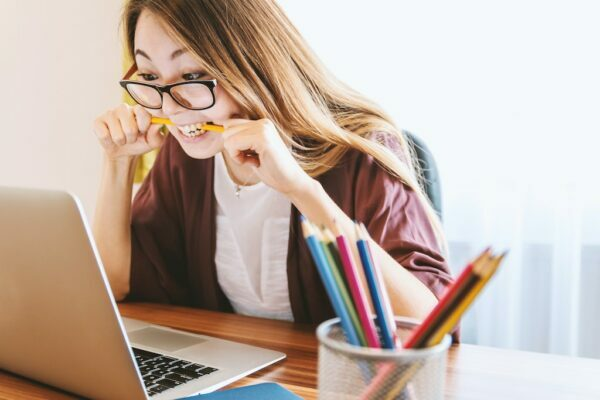 A woman at her desk, it seems she is anticipating something as she is biting a pencil excitingly