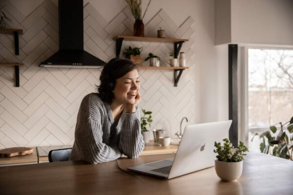 Woman at home desk on a video call and smiling