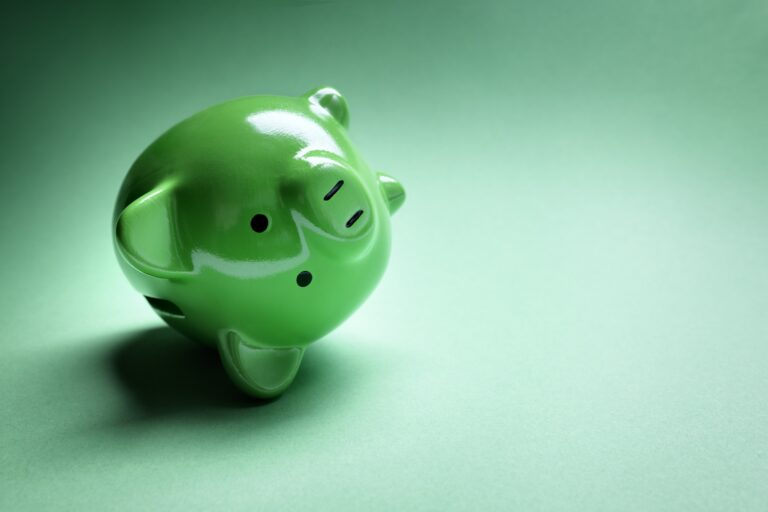 Green piggy bank on its side against green background