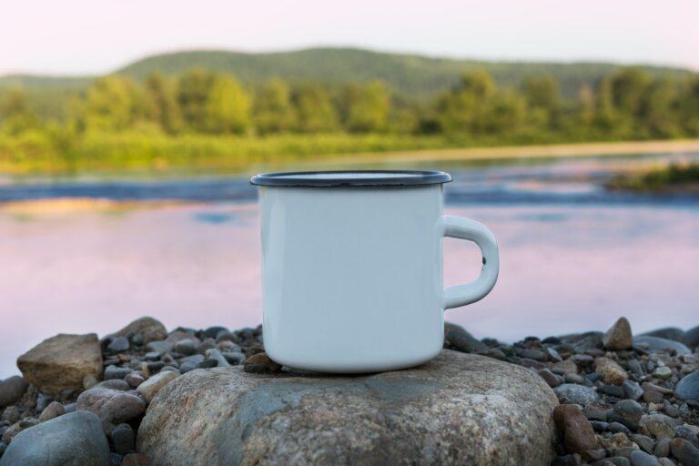 White campfire mug on a rock overlooking a lake
