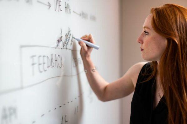 Woman writing feedback on a whiteboard