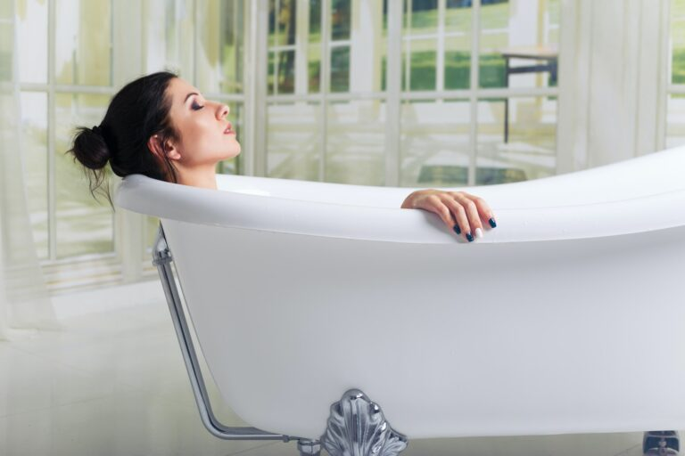 Resilience, Self care and compassion. Bathing woman relaxing in bath smiling relaxing with eyes closed