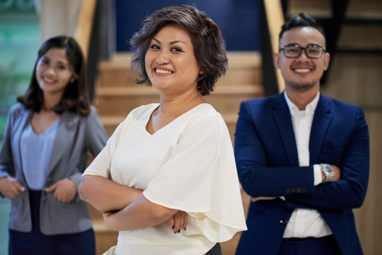 Three business people with their arms folded smiling at the camera
