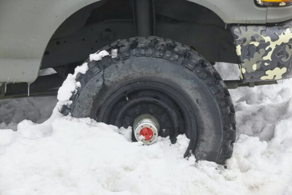 Four wheel vehicle tyre trapped on the snow. Winter time