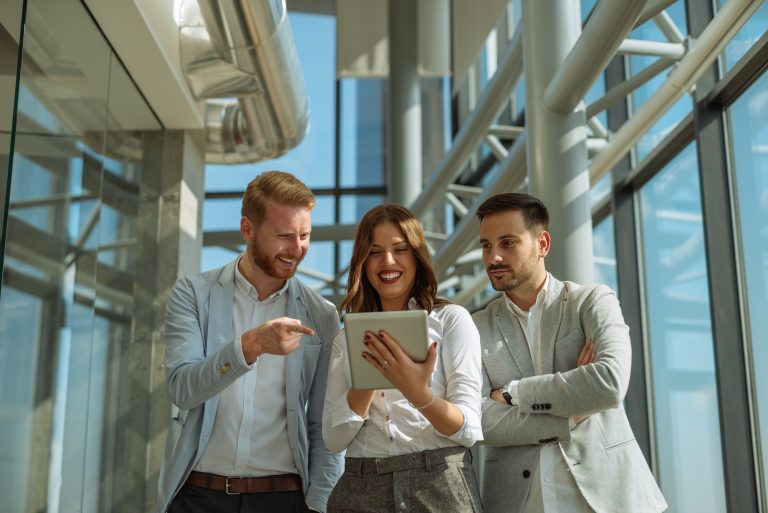 Three business people looking at a digital tablet together and smiling