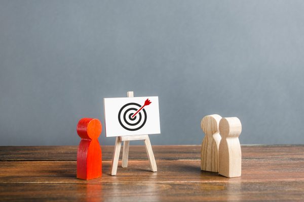 Three wooden figures looking at a bullseye on a whiteboard