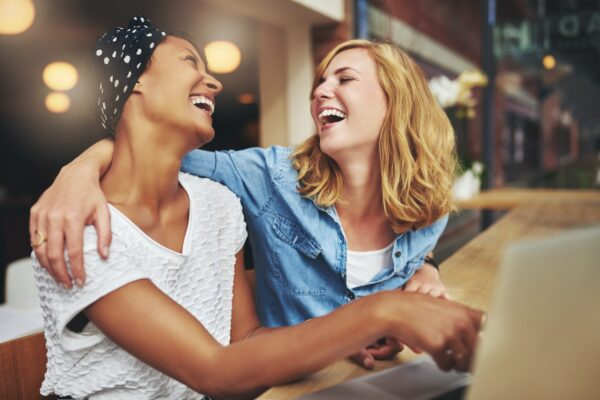 Two women with their arms around each other and laughing