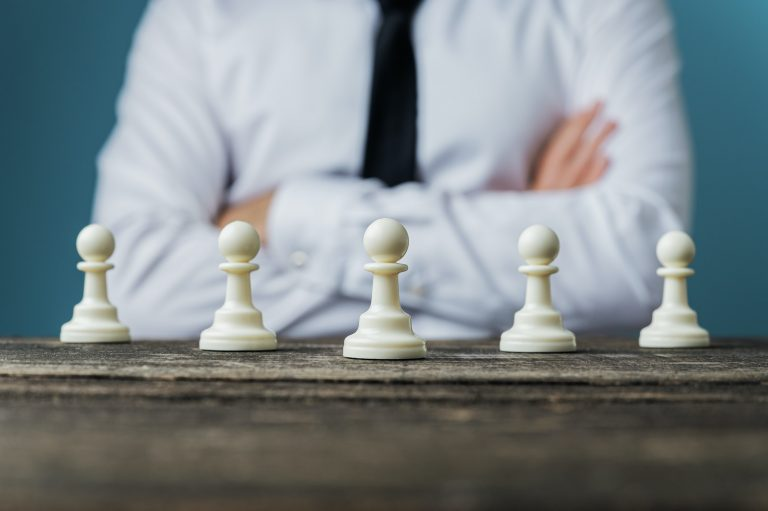 A businessman with arms folded looking at five white chess pieces