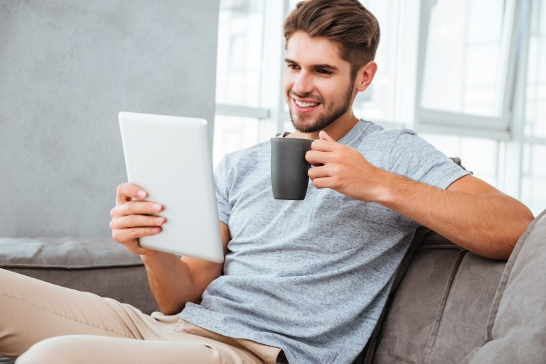 Cheerful man on a video call on tablet while drinking a coffee