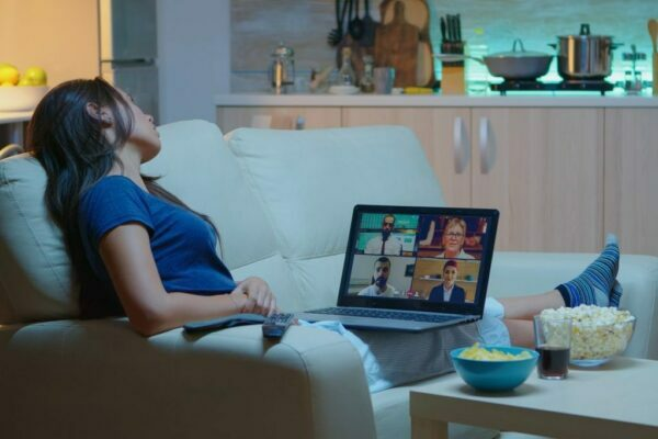 Woman sat on her sofa on a video call with two people