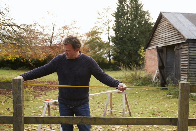 Man using a tape measure to measure his fence for repair