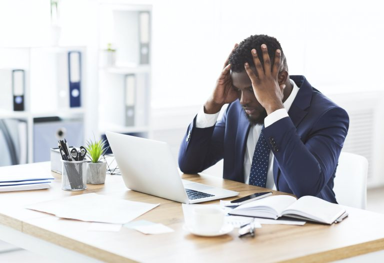 Businessman sitting at desk looking stressed with hands on head