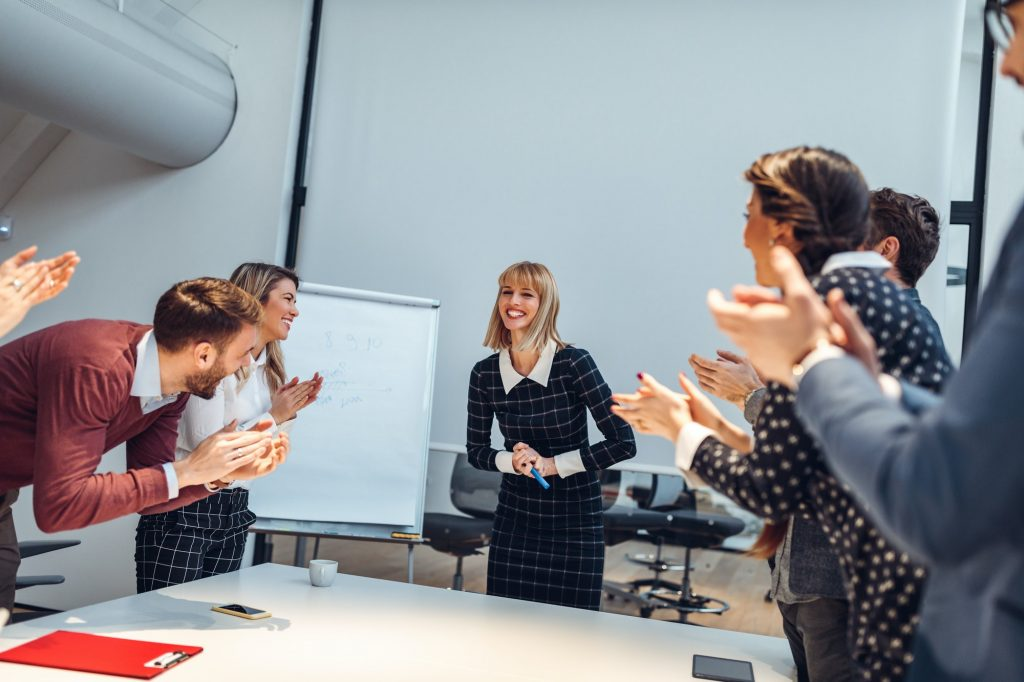 A group of business people clapping a woman giving a presentation