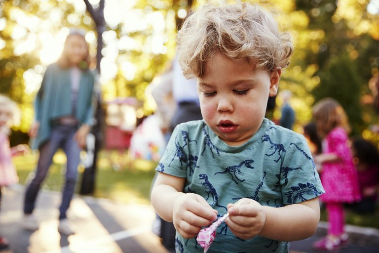 Toddler boy unwrapping a lollipop in a park outdoors
